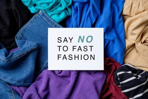 """Textiles with """"Say No To Fast Fashion"""" text overlay to shop sustainably"""
