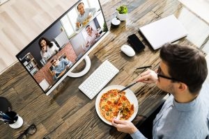 Man eating pizza during video call