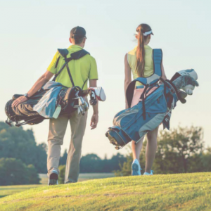 Man and woman carrying golf apparel on the course