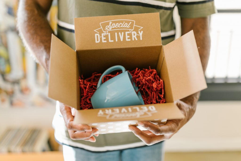 man holding delivery box with mug inside