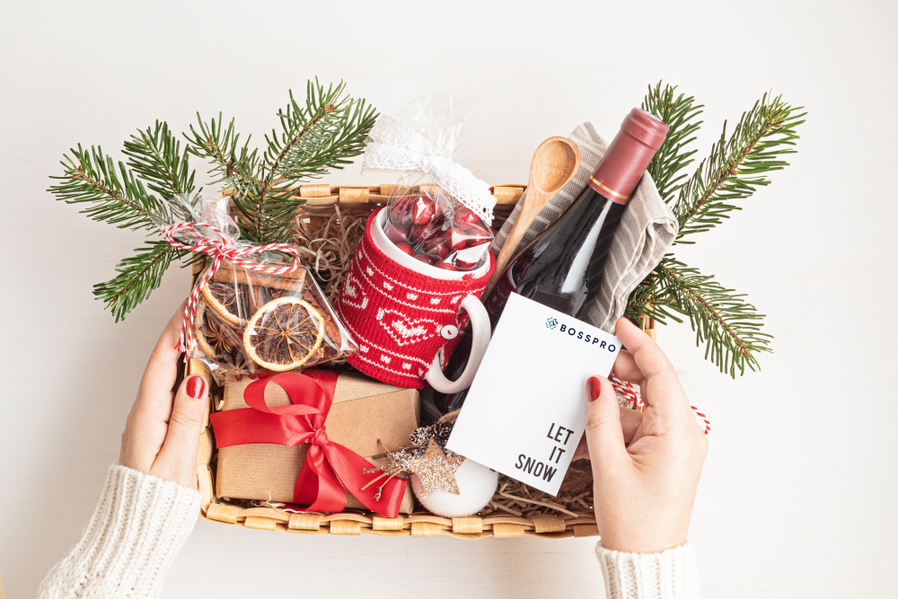Holiday gift kit in a box with greenery, wine, mug, snacks, and a crad
